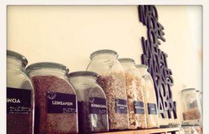 Samen, Körner und Nüsse in Glassbehältern auf einem Holzregal