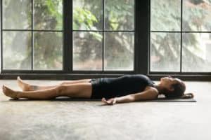 Frau liegt auf Trainingsmatte und macht Savasana, eine Yoga Entspannung