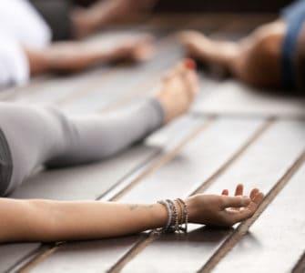 Frau liegt entspannt auf einer Yogamatte