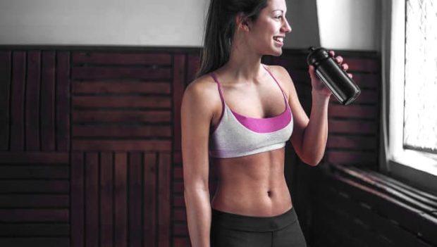 Frau in Sportkleidung trinkt aus einer Flasche nach dem Fitnesstraining