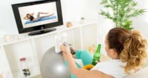 Sportlerin mit schlechten Vorsätzen vor dem Fernseher mit Bier