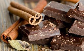 Stücken dunkler Schokolade nebst zweier Zimtstangen