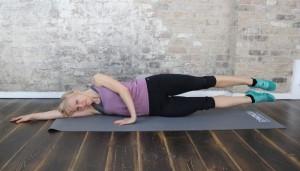 Sportliche Frau liegt auf Yogamatte vor Steinwand