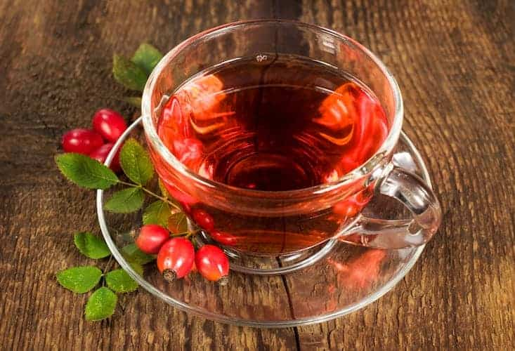 Hagebutten Tee in Glastasse auf Holztisch