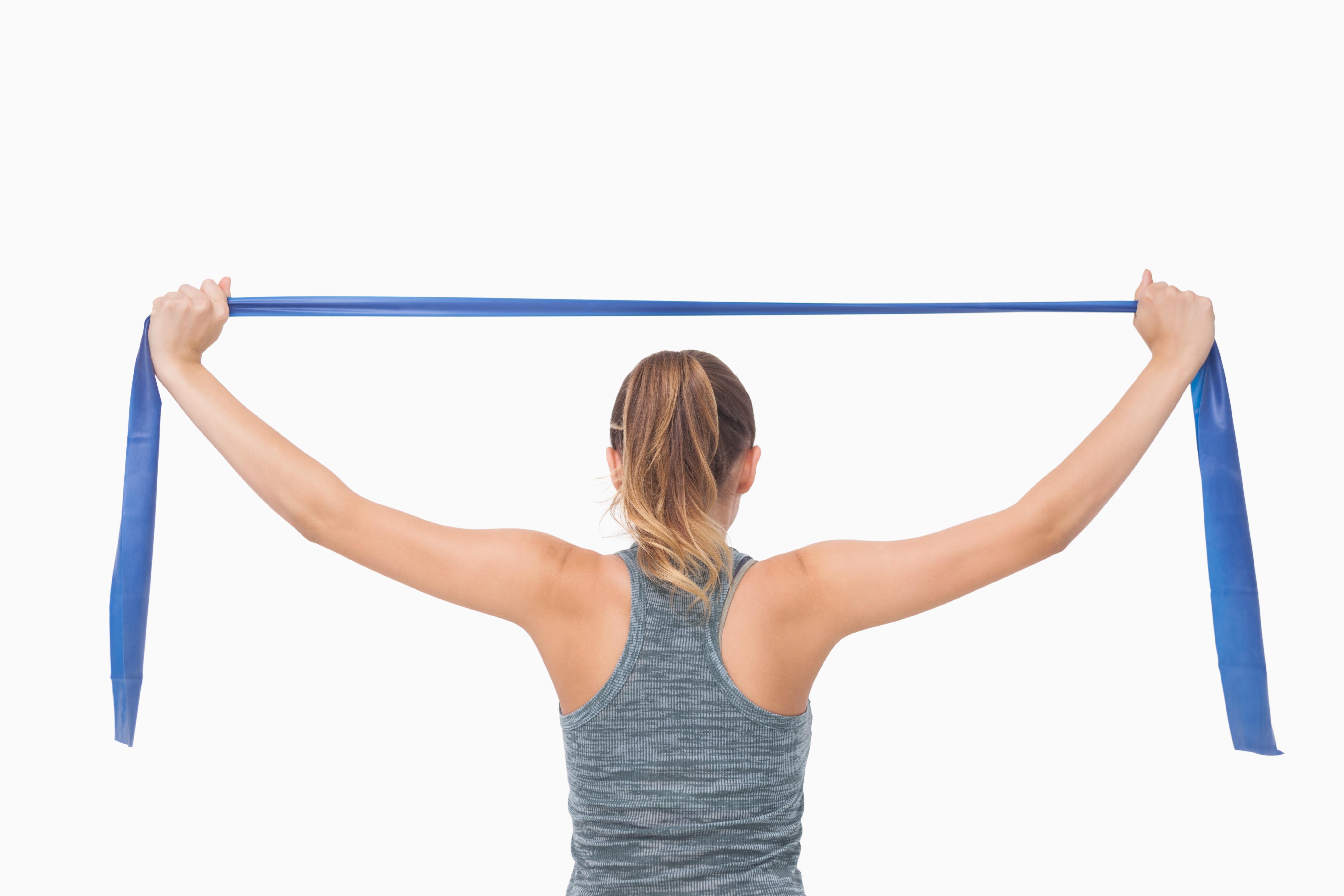 Junge Frau in hellgrauem Top von hinten zieht blaues Theraband auseinander und trainiert den Rücken