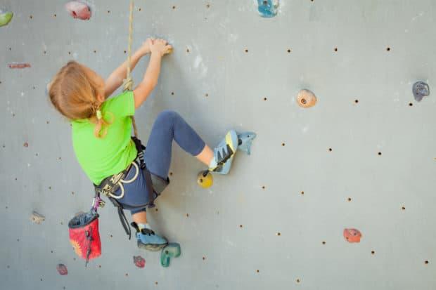 Kleines Mädchen klettert eine Wand in einem Kletterpark hoch