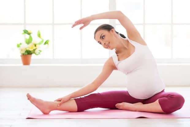 schwangere frau macht yoga seitbeuge