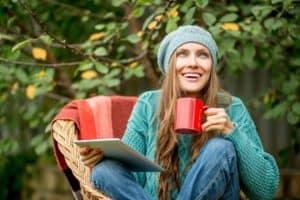 Junge Frau mit Mütze sitzt draußen in der Natur mit einer Tasse Mate Tee