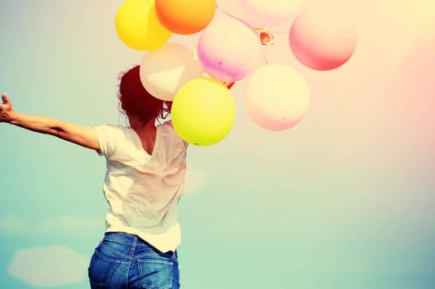 Junge Frau mit bunten Luftballons ist glücklich