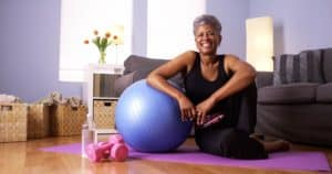 Ältere fitte Frau in Sportkleidung auf Trainingsmatte zu Hause entspannt sich nach dem Workout und lehnt sich an Pezziball