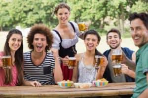 Gruppe junger Menschen sitzen an einem Holztisch und trinken Bier auf dem Oktoberfest