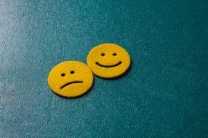 Zwei gelbe Smileys vor blauem Hintergrund. Einer lacht einer ist traurig.