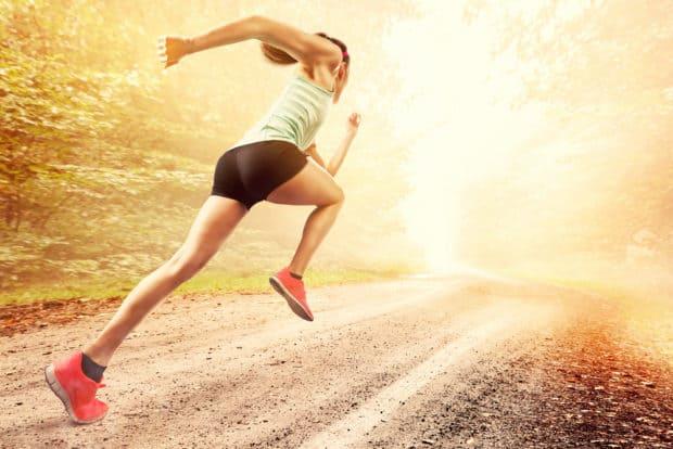 Sportliche Frau sprintet in sommerlichem Park