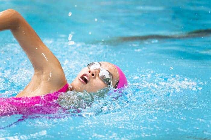 Frau schwimmt für einen gesunden Rücken