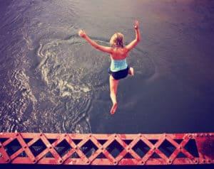 Junge Frau springt aus großer Höhe ins Wasser