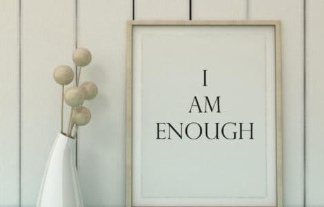 Weißes Bild mit hellem Rahmen darin steht der Schriftzug I AM ENOUGH