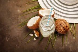 Glas mit Kokoswasser und Strohhalm zwischen frischen Kokosnüssen auf dunklem Holztisch