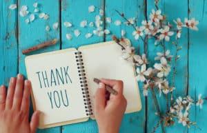 Notizbuch mit der Schrift THANK YOU darin und Hand mit Stift