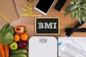 Körperwaage, Gemüse und eine Tafel mit der Aufschrift BMI