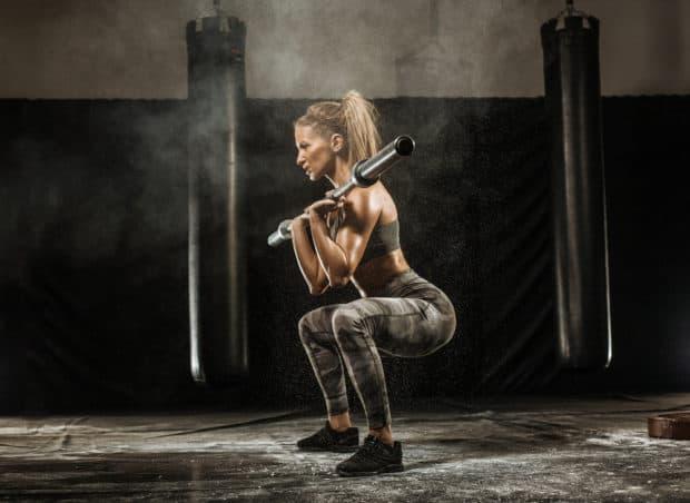 Sportliche Frau macht Kniebeuge mit Langhantel
