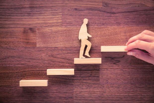 Holzhintergrund davor Männchen dass die Treppe Schritt für Schritt nach oben geht