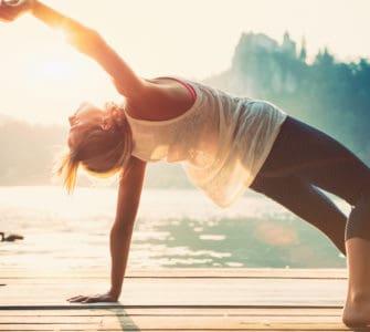 Junge Frau macht Yoga am See und fühlt sich wohl