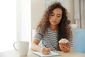 Junge Frau hält Muffin in einer Hand gleichzeitig berechnet sie mit Stift und Zettel die Kalorien