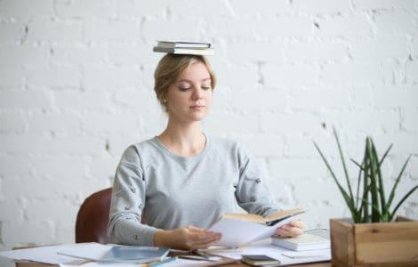Frau sitzt gerade mit einem Buch auf dem Kopf bei der Arbeit