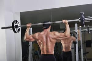 Athletischer Mann macht Schulterdrücken mit Langhantel vor Spiegel