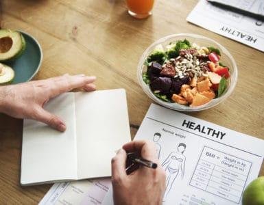 Ein Notizbuch mit Aufzeichnungen zu einer geusnden Ernährung auf einem Tisch mit gesundem Essen