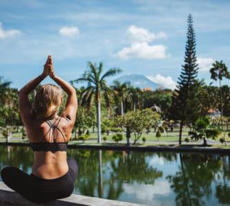 Junge Frau sitzt im Lotussitz und macht Yoga auf bali