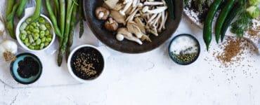 Tisch gedeckt mit Tellern voller gesunder, vegetarischer und veganer Lebensmitteln. Pilze, Sojabohnen, Gemüse