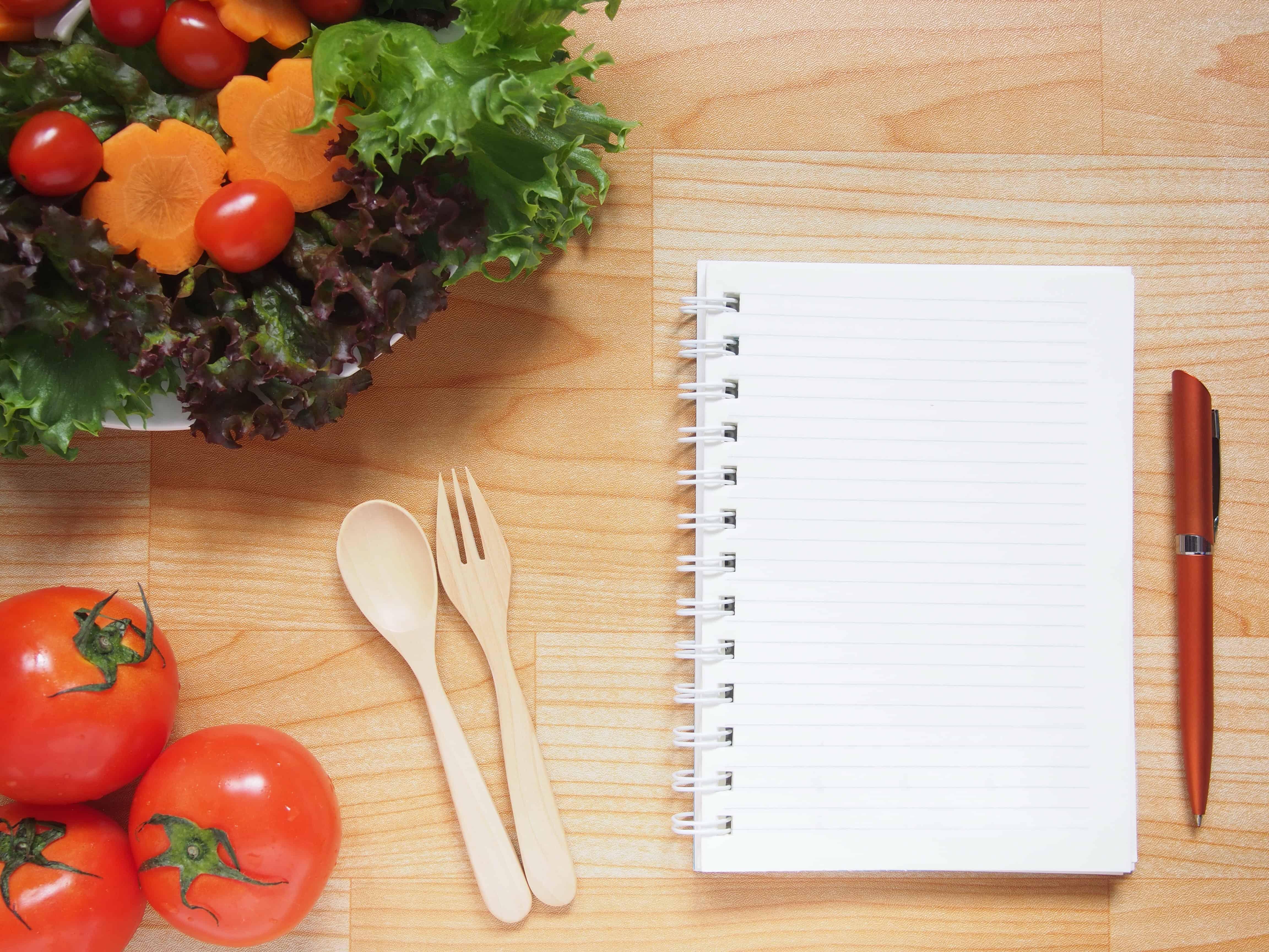 Holztisch mit gesundem frischem Gemüse und einem unbeschriebenen Ringblock mit Kuli daneben