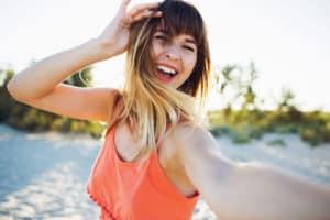 Junge Frau mit orangenem Trägretkleid lacht und ist glücklich