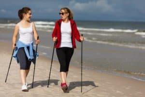 2 Frauen am Strand machenNordic Walking und lächeln sich an