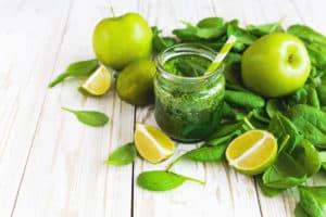 Glas mit grünem Smoothie, grüne Blätter daneben und aufgeschnittene Limetten