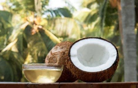 Kokosnusshälfte auf Tisch und Schale aus Glas gefüllt mit Kokosöl