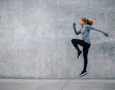 Junge Frau in sportlichem Outfit trainiert vor grauer Steinwand. Sie macht HIIT, den Fitness Trends 2018