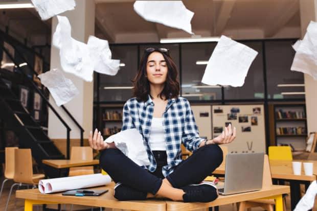 Junge Frau sitzt im Schneidersitz auf Schreibtisch und meditiert im stressigen Arbeitsalltag.