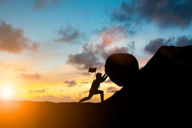 Mann rollt mit Erfolg einen schweren Stein einen Berg hoch