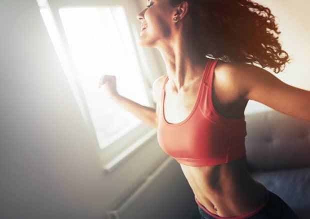 Junge Frau mit rotem Sport Top beim Training zu Hause ist glücklich