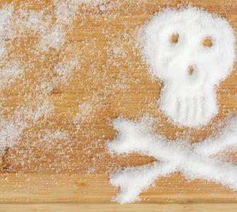 Holztisch mit Fructose Pulver in Totenkopf Form - gefährlicher Dickmacher