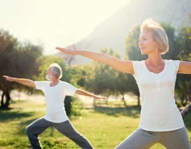 Eine Frau Mitte 50 und ihr Mann machen im Park Yogaübungen, denn Bewegung ist gesund