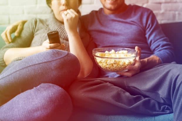 einPaar sitzt auf dem Sofa und isst poppcorn und  trinkt bier