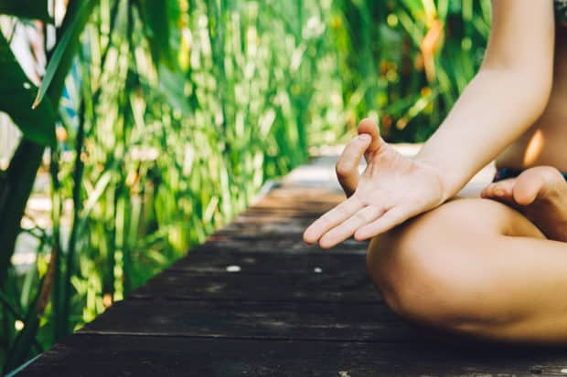 Das Knie und die Hand einer Frau im Lotussitz die Yoga macht auf Bali