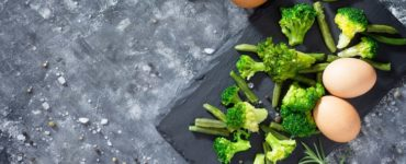 broccoli und eier auf brett dunkelgrauer tisch