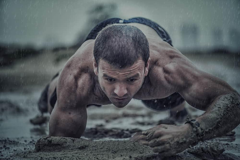 Durchtrainierter Mann macht Crawling Fitness und krabbelt durch den Schlamm