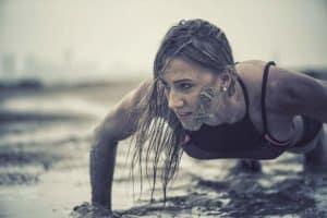 Trainierte Frau macht Crawling Fitness und krabbelt durch den Schlamm