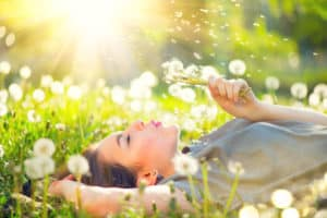 Junge Frau genießt den Moment liegt auf einer Wiese und pustet gegen eine Pusteblume.