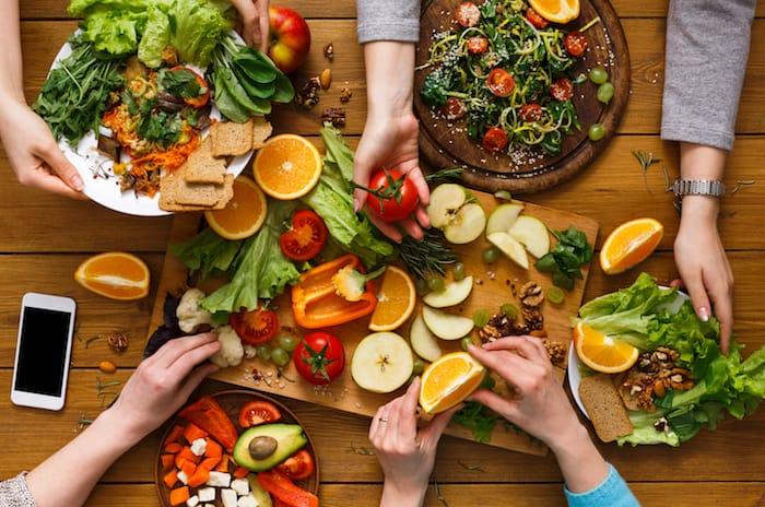 Tisch gedeckt mit Tellern voller gesunder, vegetarischer und veganer Lebensmitteln